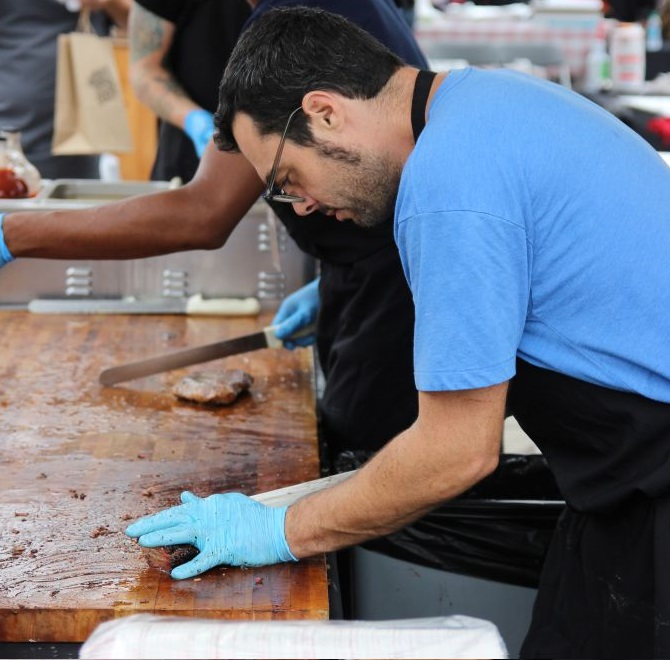 Aaron Franklin slicking brisket at the Texas Monthly BBQ Fest
