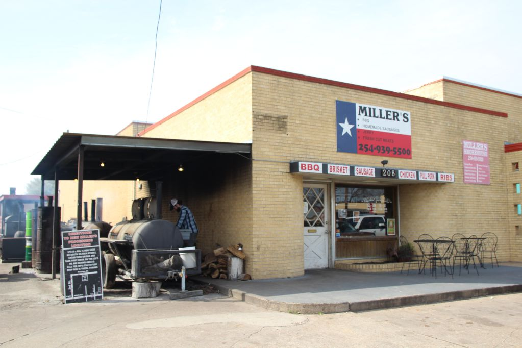 Dusty Miller tends to the pits outside of Miller's Smokehouse