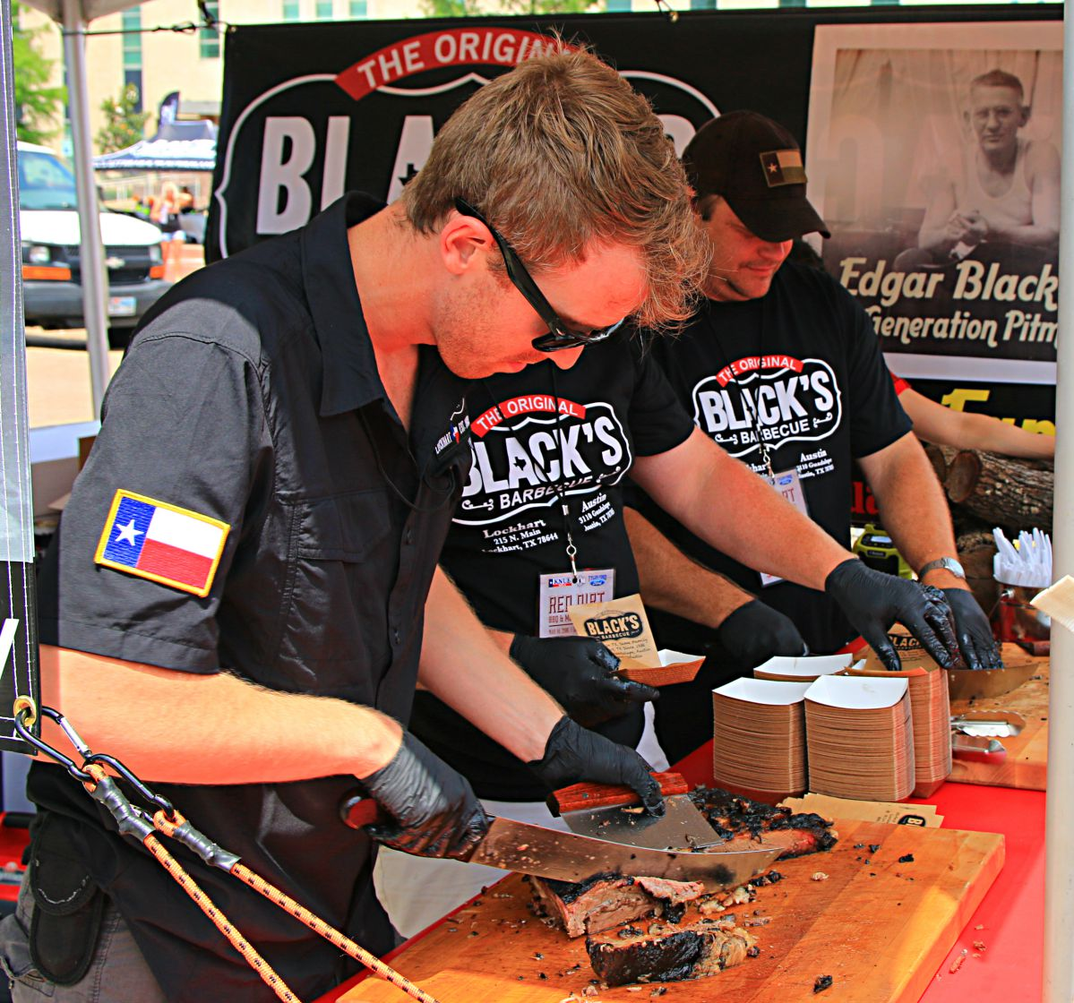 Fourth generation pitmaster Barrett Black slices brisket while an image of great grandfather Edgar Black Sr. watches over him.