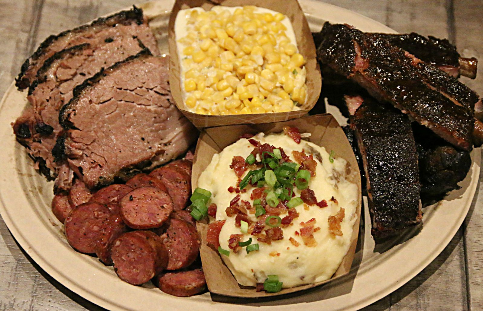 Three meat plate with sausage made in-house, mashed potatoes, and creamed corn